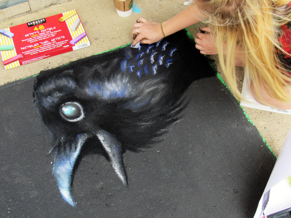 Kristine Ens working on chalk art crow